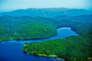 « À l'est du Canada, sur les rives d'un lac ou en pleine montagne, DTN propose des domaines privés, de 3 500 m² à 10 000 m².   S'il existe un paradis pour les amoureux de grands espaces, d'air pur et de tranquillité, le parc national du Mont Tremblant s'en approche. Nous sommes ici au Québec, sur un vaste territoire de 1 500 km, offrant plus de 400 lacs, des rivières, des cascades et des centaines de kilomètres de sentiers qui en font un cadre absolument unique. C'est à 15 minutes à peine de Tremblant, le plus grand centre de villégiature du Québec et au coeur d'un espace sauvage et naturel grandiose, que s'inscrivent ces trois domaines privés viabilisés. Le premier, Domaine Nostalgia, est situé dans une superbe forêt d'érables et de sapins, et bénéficie d'un ensoleillement total. Il se compose de 70 terrains, d'environ 4000 m² chacun. Certains, nichés sur les hauteurs, bénéficient de vues dominantes sur les montagnes alentour et sur le Mont Tremblant.  À vocation familiale, ce domaine bénéficie de nombreux aménagements : sentiers pédestres, jeux pour les enfants, espaces de loisirs, belvédère et accès aux lacs. Le second domaine, Domaine Secret Life, a la particularité d'offrir des vues panoramiques sur toute la vallée du Mont Tremblant et les grands lacs environnants. Il se caractérise également par ses grands espaces : tous les terrains font au minimum 8 000 m² et jusqu'à 15 000 m². Ultime privilège, les propriétaires ont accès aux lacs de pêche privés, situés en contrebas de la propriété. Enfin, Domaine Port d'Attache est un territoire de prestige, situé en bordure du grand Lac aux Quenouilles, lac navigable et accessible aux engins motorisés. Certains terrains limitrophes disposent d'un accès direct privé tandis que d'autres, plus en retrait, bénéficient d'un accès par une partie commune. Tous jouissent en tout cas de superbes vues sur le lac.   L'AVIS DE FRANCK IACOMACCI Responsable des ventes pour la France de DTN   Indicateur Bertrand : Quelle est la particu